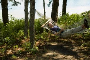 ハンモックの上で転寝する男性の写真素材 [FYI03953331]