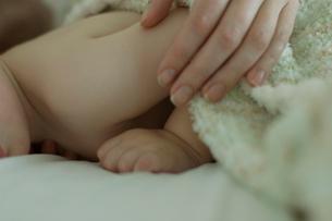 ベッドで寝ている男の子と母親の手の写真素材 [FYI03953358]