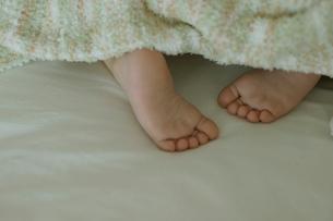 ベッドで寝ている男の子の足の写真素材 [FYI03953359]