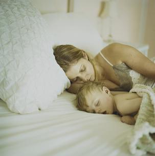 ベッドで寝ている男の子と母親の写真素材 [FYI03953364]