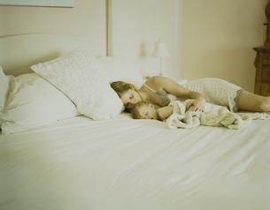 ベッドで寝ている男の子と母親の写真素材 [FYI03953367]
