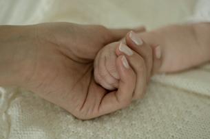 ベッドで寝ている男の子と母親の手の写真素材 [FYI03953368]