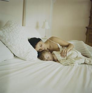 ベッドで寝ている男の子と母親の写真素材 [FYI03953369]