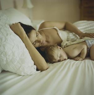 ベッドで寝ている男の子と母親の写真素材 [FYI03953370]