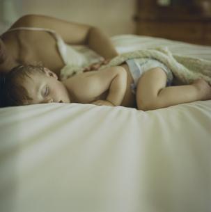 ベッドで寝ている男の子と母親の写真素材 [FYI03953371]