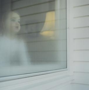 曇り窓から外を眺める女の子の写真素材 [FYI03953446]