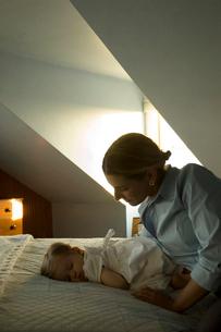 ベッドに寝ている女の子と母親の写真素材 [FYI03953449]