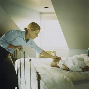 ベッドに寝ている女の子と母親の写真素材 [FYI03953460]