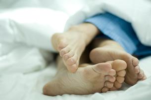 ベッドで寄り添って寝ているカップルの足の写真素材 [FYI03953474]