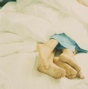ベッドで寄り添って寝ているカップルの足の写真素材 [FYI03953480]