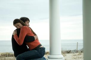 ポーチで抱き合いながら座っているカップルの写真素材 [FYI03953504]