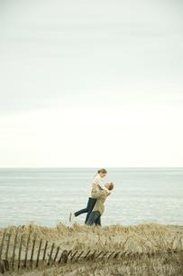 浜辺ではしゃぐカップルの写真素材 [FYI03953509]