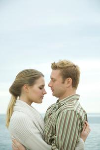 浜辺で寄り添っているカップルの写真素材 [FYI03953510]
