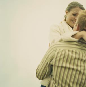 浜辺で抱き合いはしゃぐカップルの写真素材 [FYI03953517]