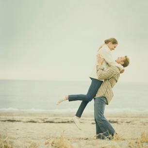 浜辺で抱き合いはしゃぐカップルの写真素材 [FYI03953518]