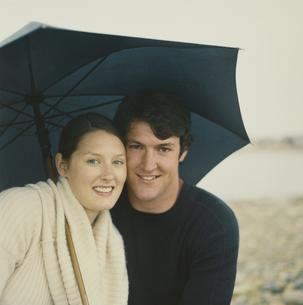海岸で傘をさすカップルの写真素材 [FYI03953524]