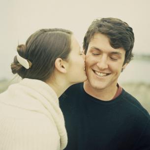 男性の頬にキスをする女性の写真素材 [FYI03953528]