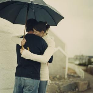 傘をさし抱き合うカップルの写真素材 [FYI03953530]
