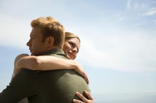 空の下で抱き合うカップルの写真素材 [FYI03953535]