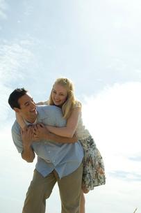 草原の中で寄り添ってはしゃぐカップルの写真素材 [FYI03953560]