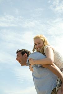 草原の中で寄り添ってはしゃぐカップルの写真素材 [FYI03953561]