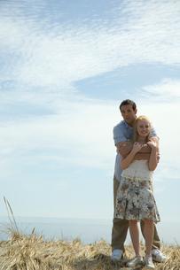 草原の中で寄り添うカップルの写真素材 [FYI03953562]
