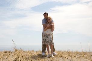 草原の中で寄り添うカップルの写真素材 [FYI03953564]