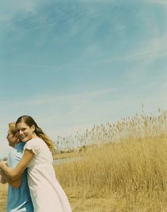 草原の中で寄り添うカップルの写真素材 [FYI03953565]