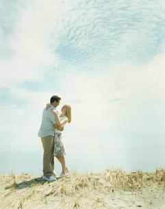 草原の中で寄り添うカップルの写真素材 [FYI03953571]