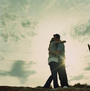夕日の中で抱き合うカップルの写真素材 [FYI03953579]