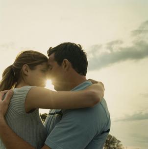 夕日の中で抱き合うカップルの写真素材 [FYI03953580]