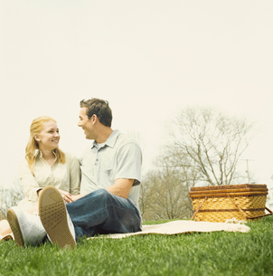芝生でピクニックをするカップルの写真素材 [FYI03953595]