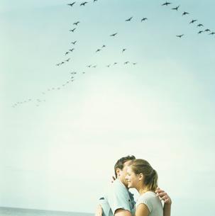 鳥が舞う空の下で抱き合うカップルの写真素材 [FYI03953597]