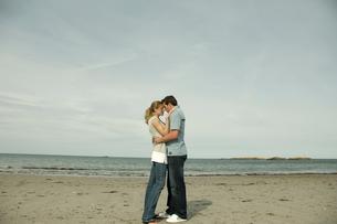 浜辺で寄り添うカップルの写真素材 [FYI03953598]