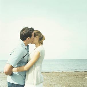 浜辺で寄り添うカップルの写真素材 [FYI03953600]