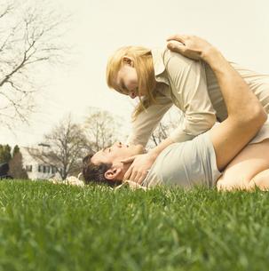 芝生に横になり寄り添うカップルの写真素材 [FYI03953602]