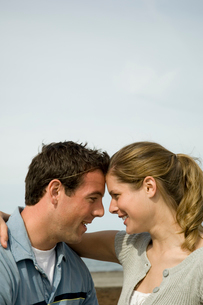 海岸で寄り添い笑いあうカップルの写真素材 [FYI03953607]