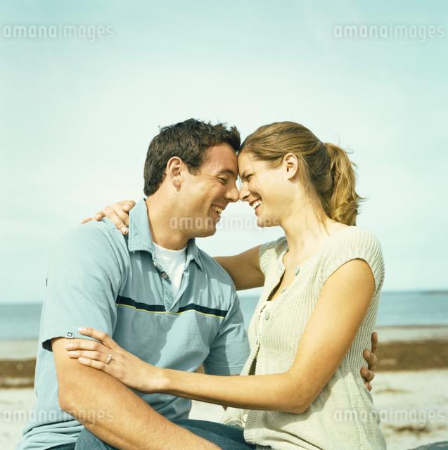 海岸で寄り添い笑いあうカップルの写真素材 [FYI03953608]