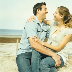 海岸で寄り添い笑いあうカップルの写真素材 [FYI03953610]