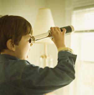 望遠鏡で窓の外を見ている少年の写真素材 [FYI03953626]