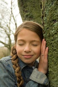 眼を閉じて木に耳を当てている少女の写真素材 [FYI03953629]
