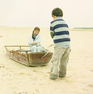 砂浜にある壊れたボートで遊ぶ男の子と女の子の写真素材 [FYI03953644]