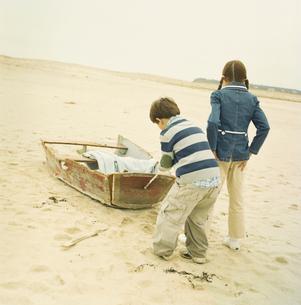 砂浜にある壊れたボートで遊ぶ男の子と女の子の写真素材 [FYI03953646]