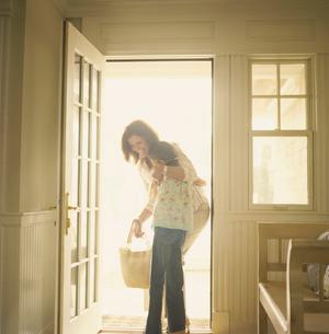 玄関先で孫娘を抱き寄せる祖母の写真素材 [FYI03953649]