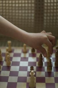 椅子の上でチェスをする少年の写真素材 [FYI03953651]