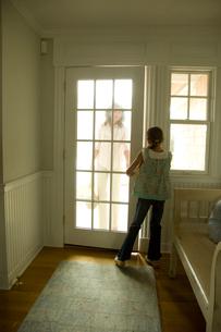 祖母の帰宅でドアを開ける孫娘の写真素材 [FYI03953654]
