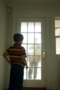 ドアの外にいる祖父を見る孫息子の写真素材 [FYI03953661]