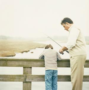 湖で釣りをする祖父と孫息子の写真素材 [FYI03953689]