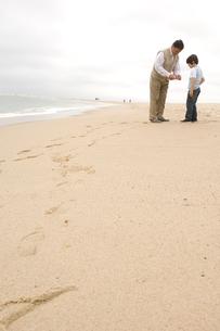 浜辺に立っている祖父と孫息子の写真素材 [FYI03953692]