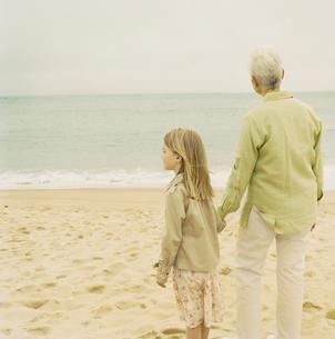 浜辺で手を繋ぐ祖母と孫娘の写真素材 [FYI03953695]